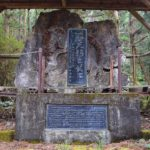 Stone monument celebrating logging history of forest